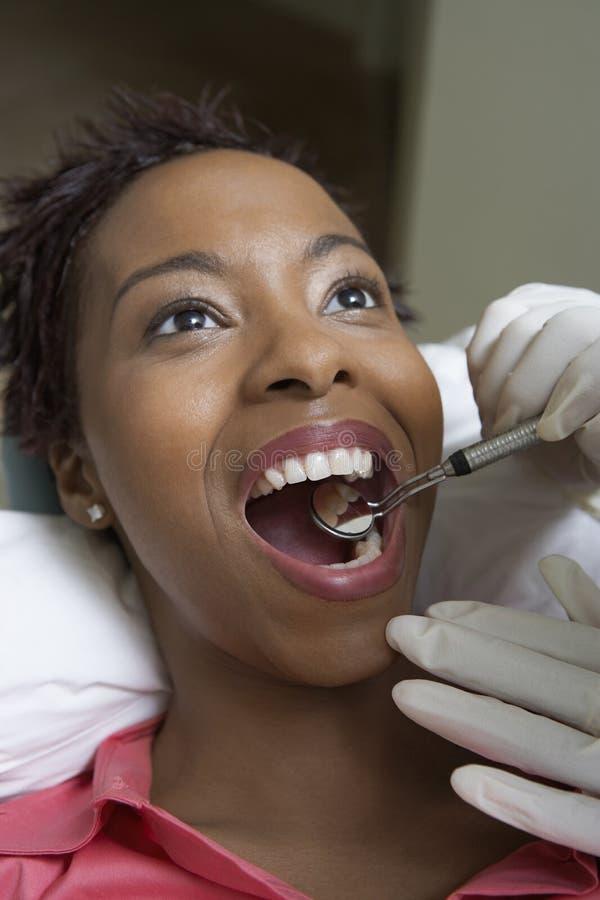 Woman Having Dental Checkup. Female patient receiving dental checkup from dentist stock images