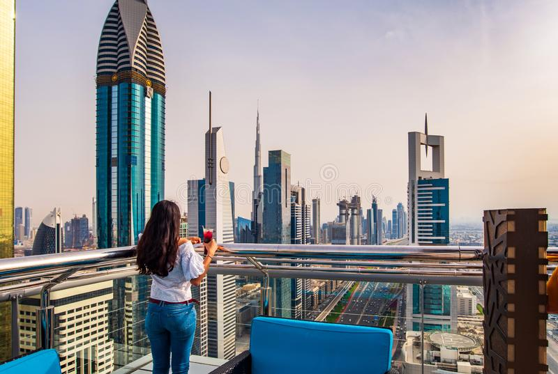 Woman having a drink with Dubai city view. Woman having a drink and enjoying Dubai city view stock images