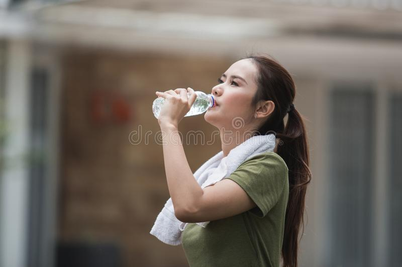 Woman having a drink after exercising. Attractive young asian woman having a drink after exercising stock photo