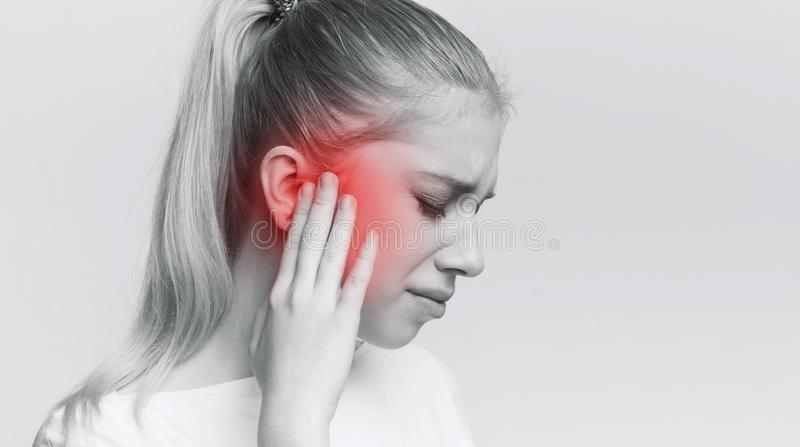 Woman having ear pain, touching her painful head. Young woman with sore ear, suffering from otitis, black and white panorama with red accent, free space stock photo