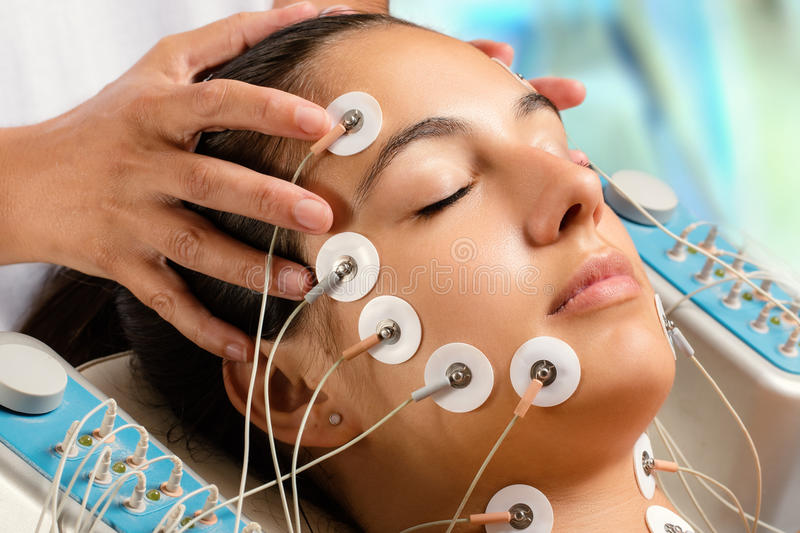 Woman having electrical facial skin tightening treatment. stock images
