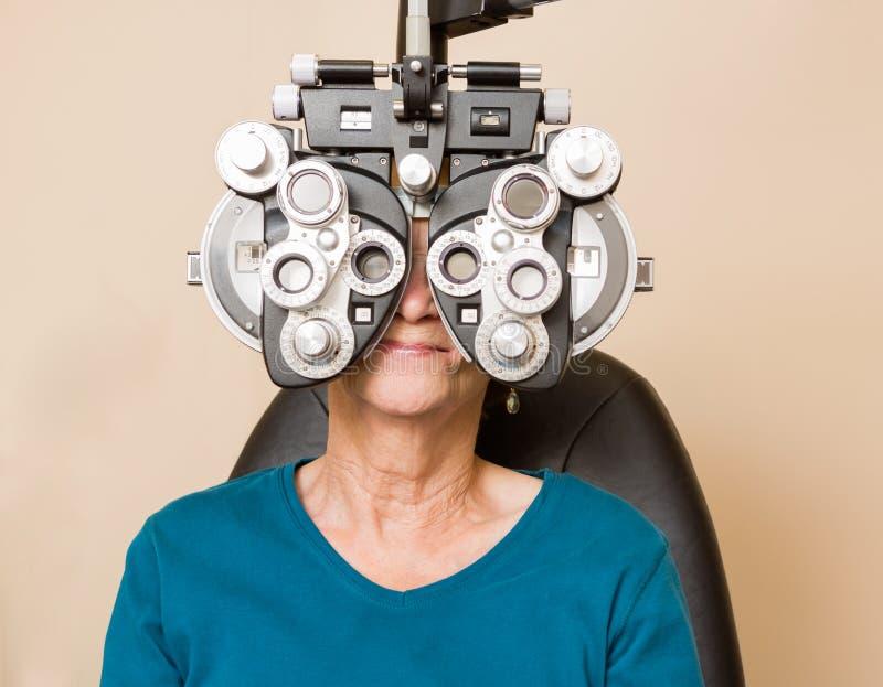 Woman Having An Eye Exam. Senior woman looking through phoropter during eye exam royalty free stock photo