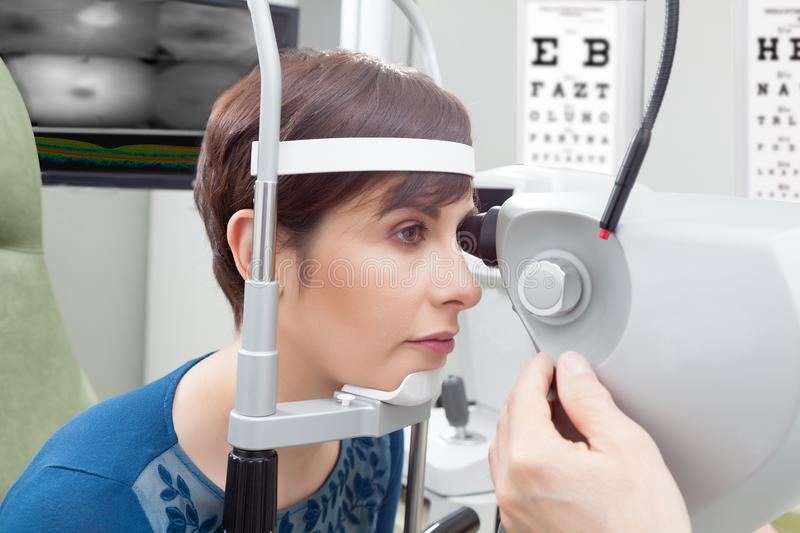 Woman having eye examination. Woman with short haircut close-up from her side having eye examination at ophthalmology room in hospital, male oculist hand stock images