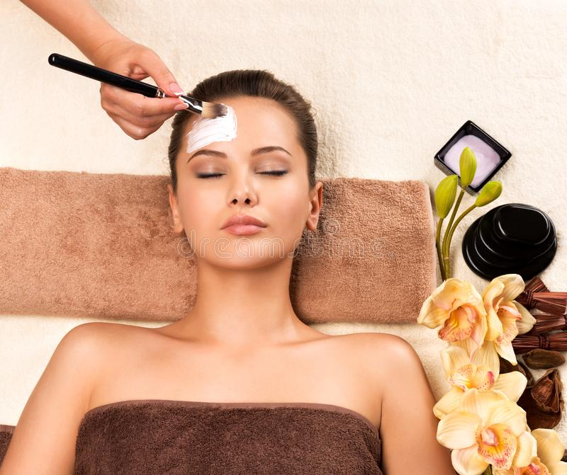 Woman having a facial cosmetic mask at spa salon. Beautiful young woman having a facial cosmetic mask at spa salon royalty free stock images
