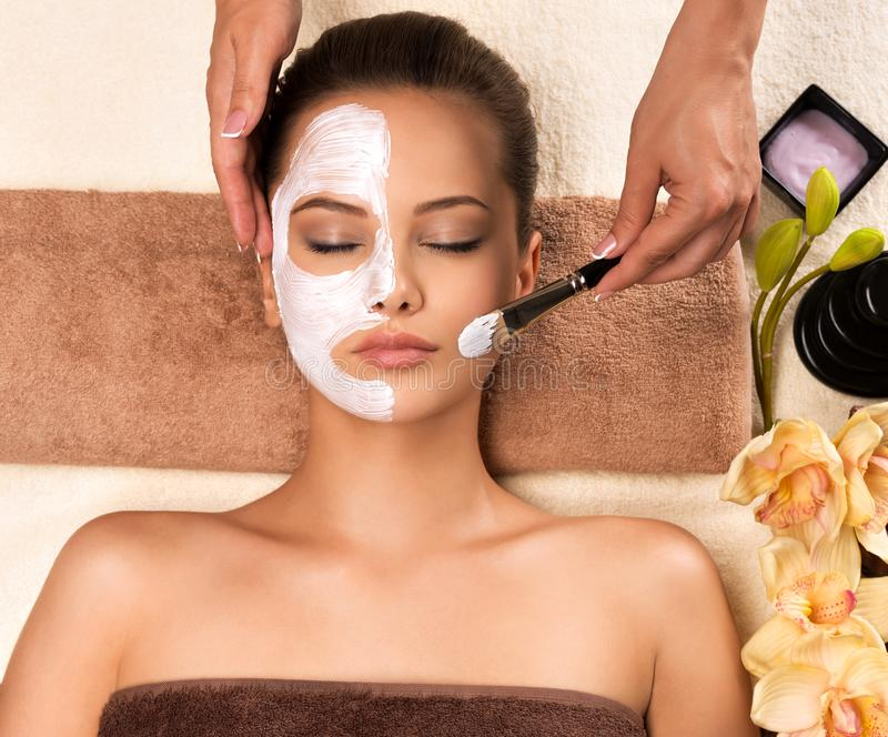 Woman having a facial cosmetic mask at spa salon. Beautiful young woman having a facial cosmetic mask at spa salon stock image