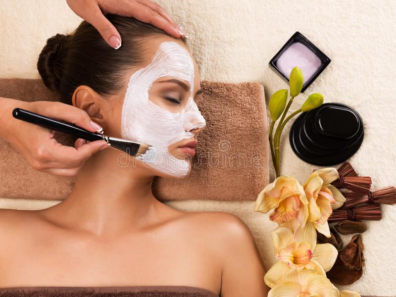 Woman having a facial cosmetic mask at spa salon. Beautiful young woman having a facial cosmetic mask at spa salon royalty free stock photo