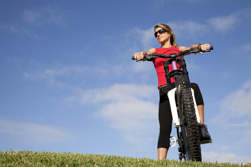 Woman having fun on a bicycle royalty free stock photography