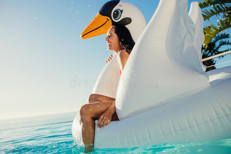 Woman having fun on floating toy in pool stock images