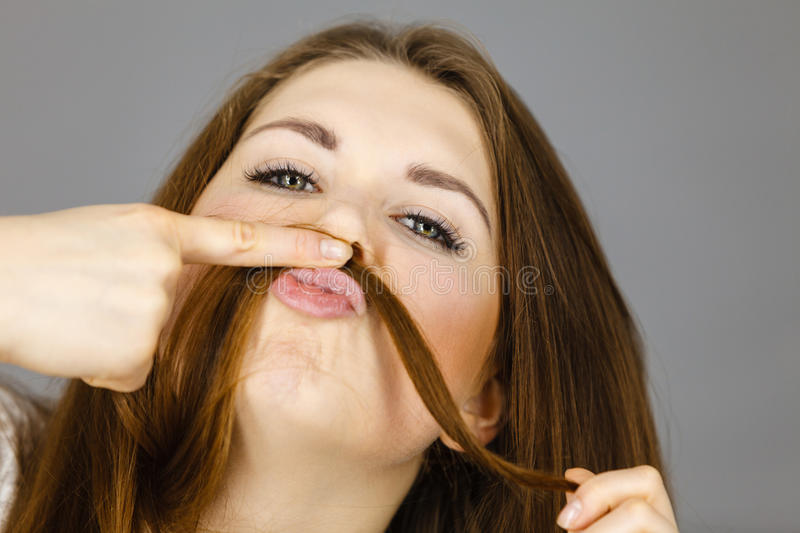 Woman having fun with her hair making moustache. Woman having fun with her long brown hair making moustache being happy about hairdo condition, studio shot grey stock images
