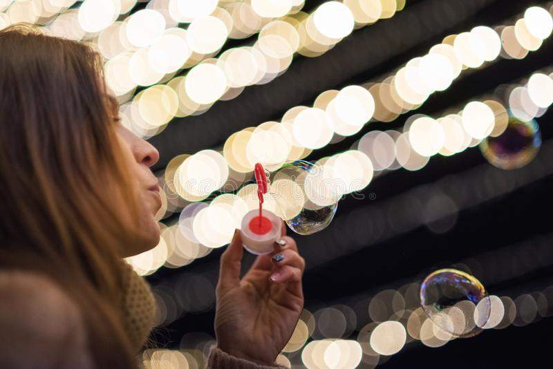 Woman having fun making soap bubbles at night party or new year eve celebration stock photography