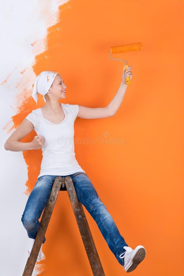 Woman having fun while painting. Woman sitting on ladder and having fun while painting wall royalty free stock photos
