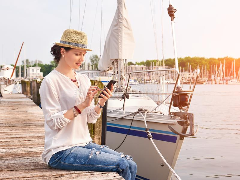 Woman in seaport chatting on smartphone with yachts on background. royalty free stock photos