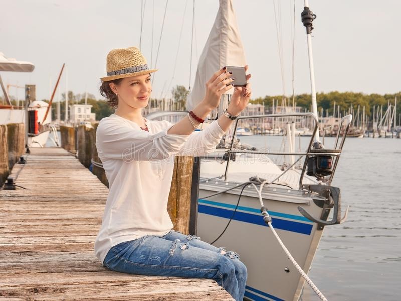 Woman in seaport making selfie with yachts on background. royalty free stock photography