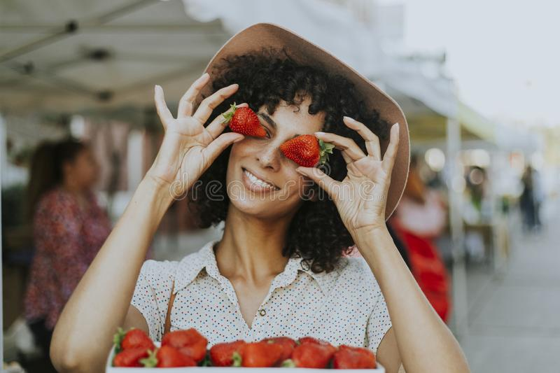 Woman having fun with strawberries stock photography
