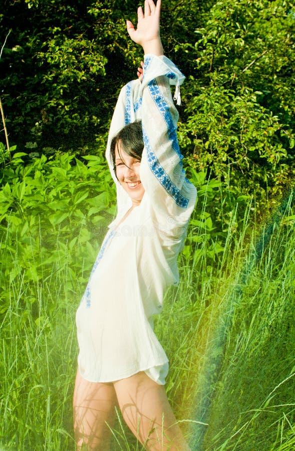 Woman having fun in summer rain. Young woman in ethnic blouse having fun in sunny summer rain royalty free stock photos