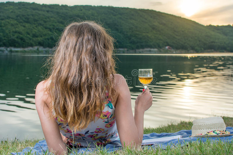 Woman having glass of wine by the lake stock photos
