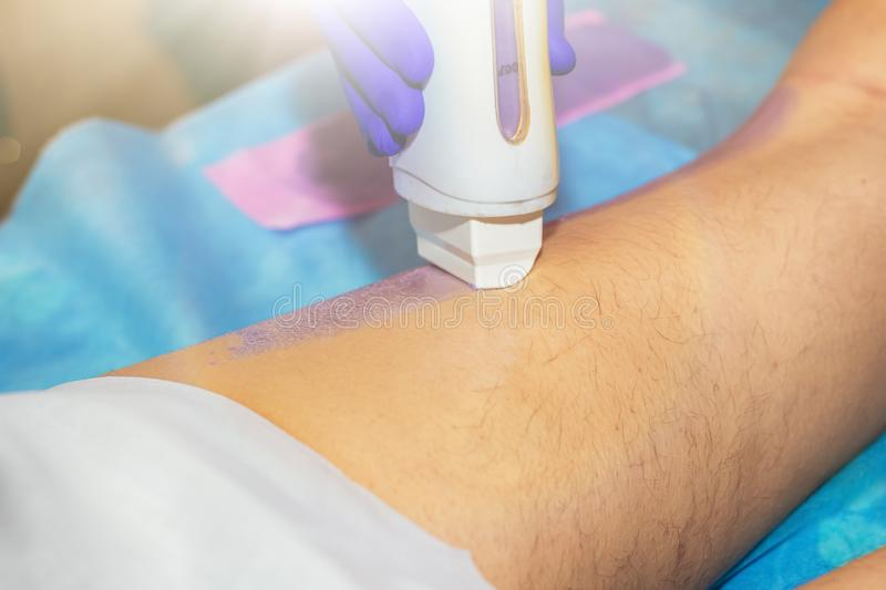 Woman having hair removal procedure on leg with wax depilatory in salon. Depilation concept.  royalty free stock photo