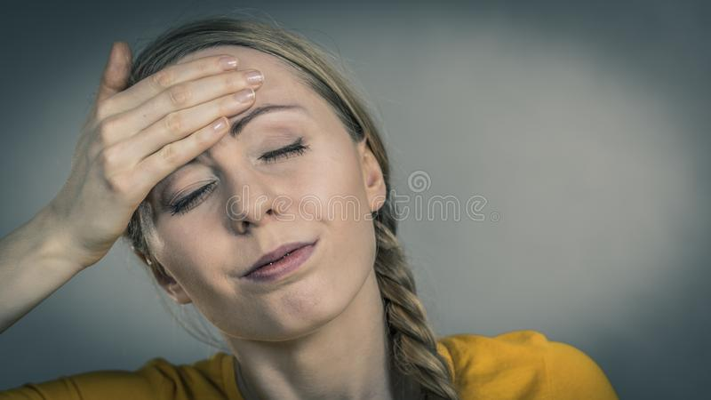 Woman having head ache. Young blonde woman having serious migrene suffering from horrible head ache feeling big pain stock image