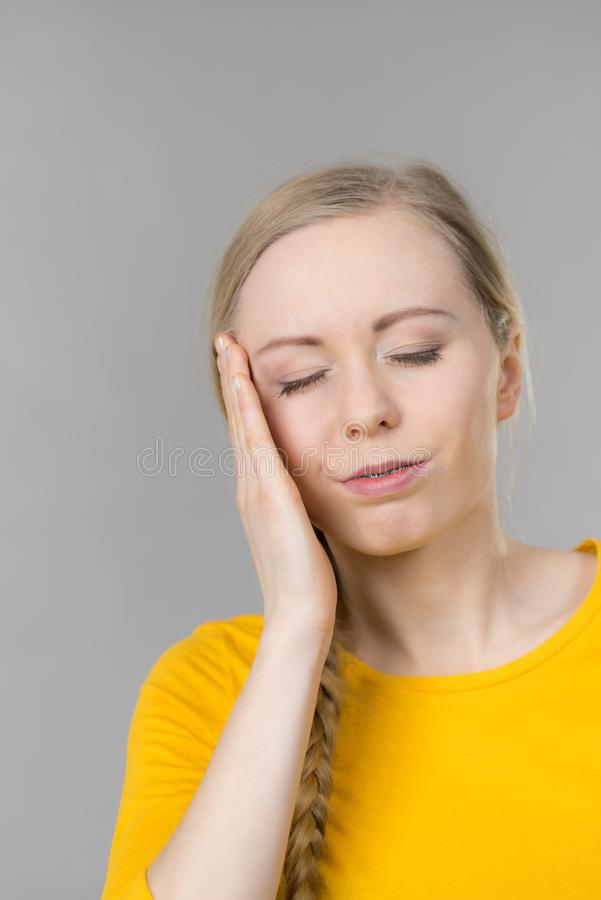 Woman having head ache. Young blonde woman having serious migrene suffering from horrible head ache feeling big pain royalty free stock images