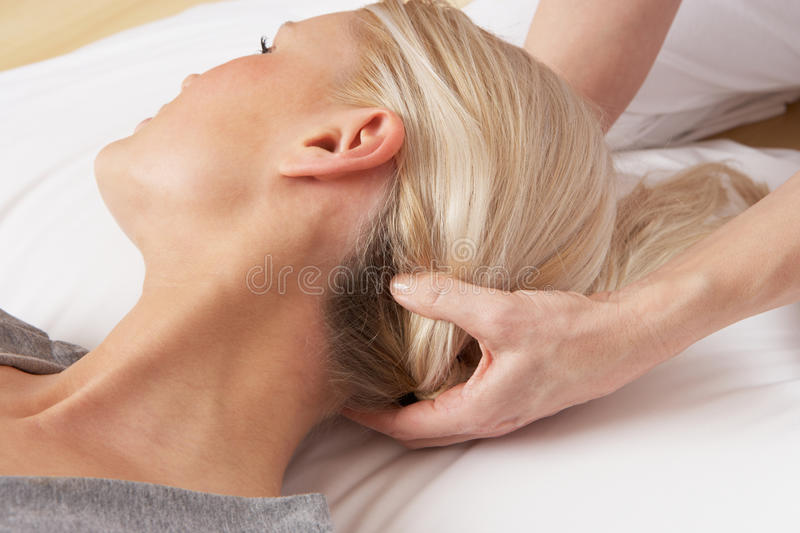 Woman having head massage by professional. On exercise mat royalty free stock images