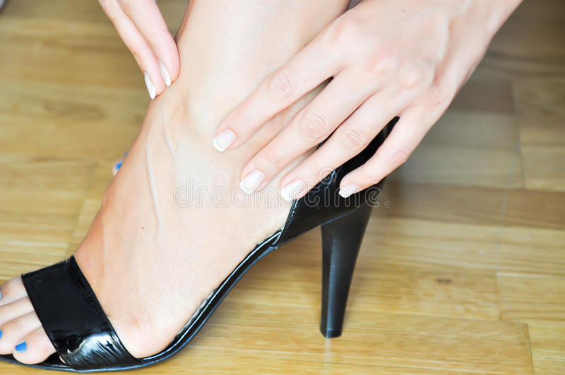 Woman having heel or ankle pain. In the office royalty free stock photo