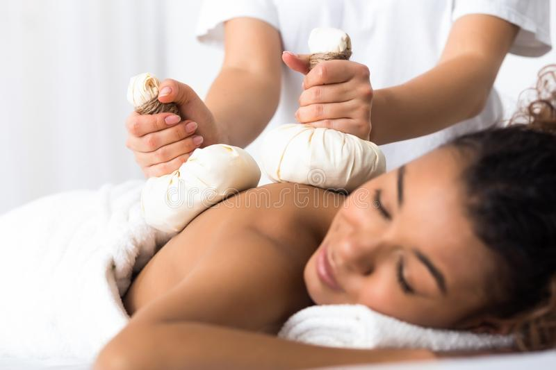 Woman having herb compress massage in beauty spa stock images