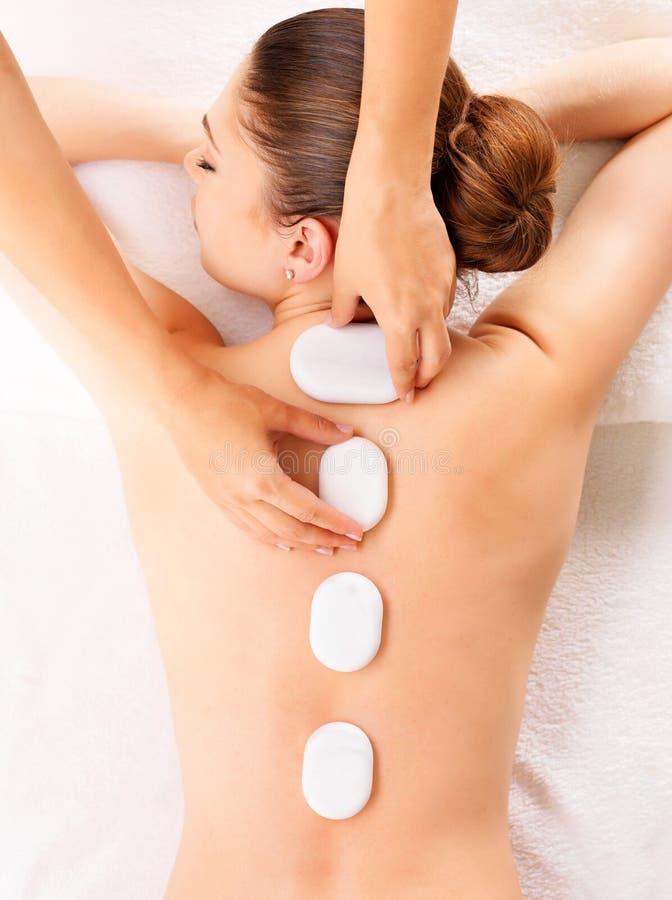 Woman having hot stone massage in spa salon. Young woman having hot stone massage in spa salon. Beauty treatment concept stock image