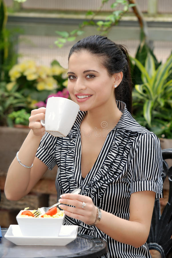Woman having lunch in outdoor cafe. Portrait of a woman having lunch in outdoor cafe drinking coffee stock photo