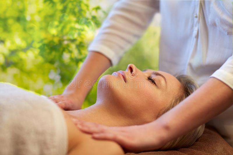 Woman having massage in spa. Beauty, wellness and relaxation concept - beautiful young woman lying having massage in spa over green natural background royalty free stock photo