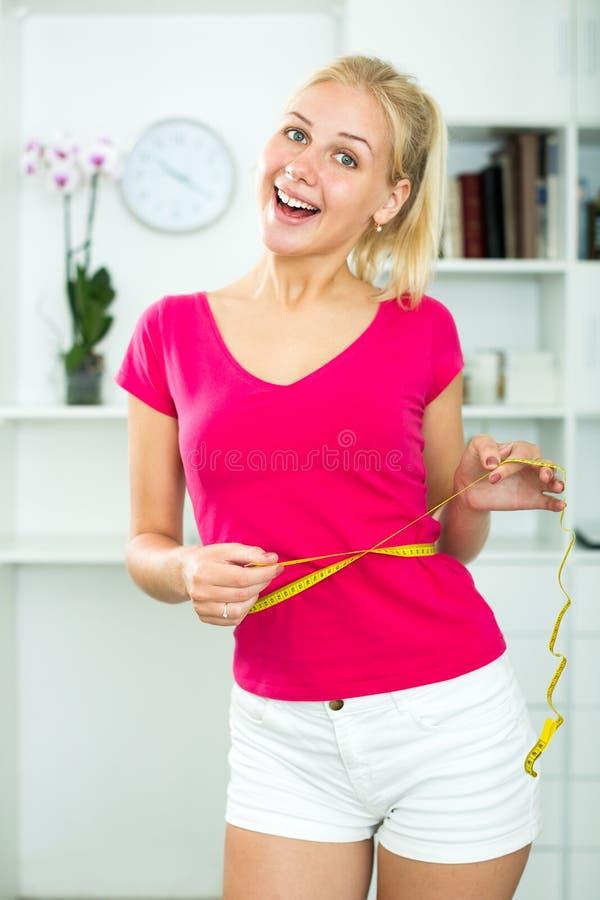 Woman having measuring tape around her waist. Positive young blond woman having measuring tape around her waist indoors in light interior royalty free stock photo