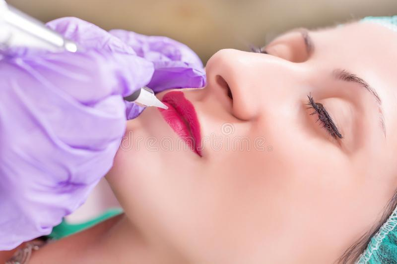 Woman having permanent makeup on lips in beautician salon stock photos