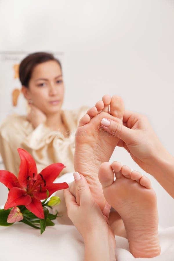 Woman Having Reflexology. Hands of a reflexologist doing reflexology treatment on the soles of a womans feet royalty free stock photography