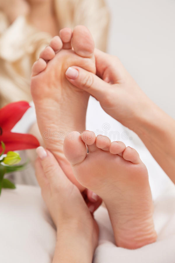 Woman Having Reflexology. Hands of a reflexologist doing reflexology treatment on the soles of a womans feet royalty free stock images