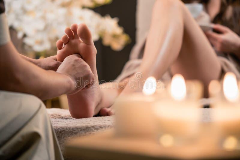 Woman having reflexology foot massage in wellness spa. Center stock photo