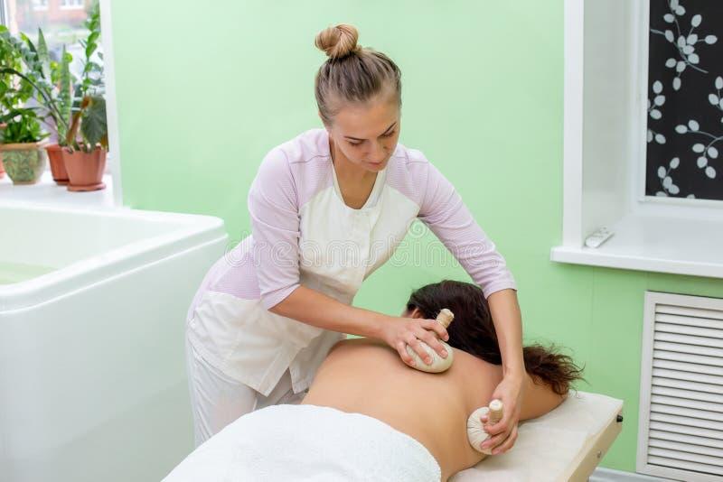 Woman having spa bags massage in wellness salon. Closeup royalty free stock photography