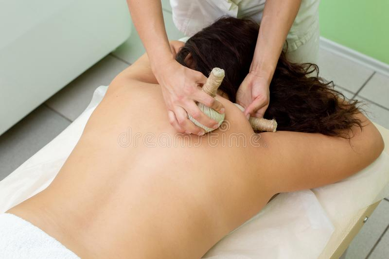 Woman having spa bags massage in wellness salon stock photos