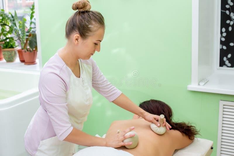 Woman having spa bags massage in wellness salon. Closeup royalty free stock photo