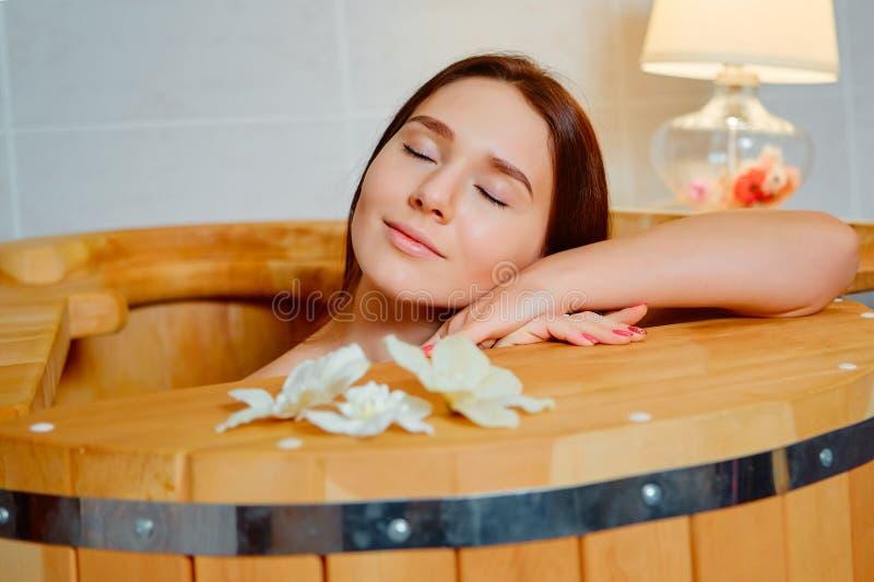Woman having spa treatment and relaxing in wooden hot barrel sauna, cedar bathtub stock images