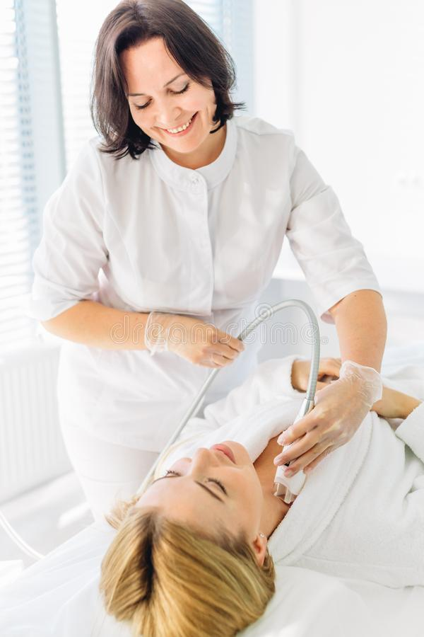 Woman having a stimulating facial treatment from a therapist. Attractive young groomed women pampers herrself with a facial or a body treatment in a luxury spa royalty free stock photo