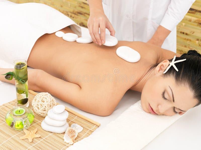 Woman having stone massage of back in salon. Woman having hot stone spa massage of back in beauty salon royalty free stock photos