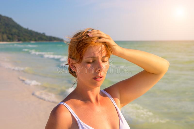 Woman having sun stroke on sunny beach. Woman on hot beach with sunstroke. Health problem on holiday. Medicine on vacation. Dangerous sun. Beach life royalty free stock images