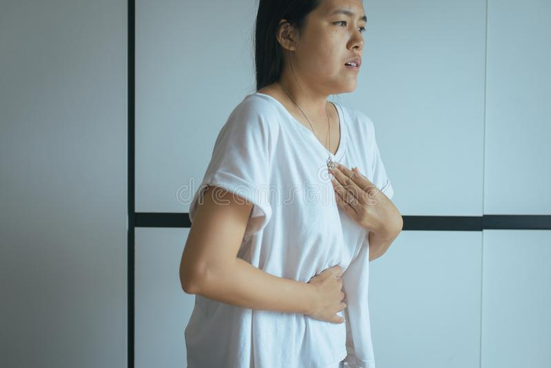 Woman having or symptomatic reflux acids,Gastroesophageal reflux disease,Because the esophageal sphincter that separates the esoph stock photo