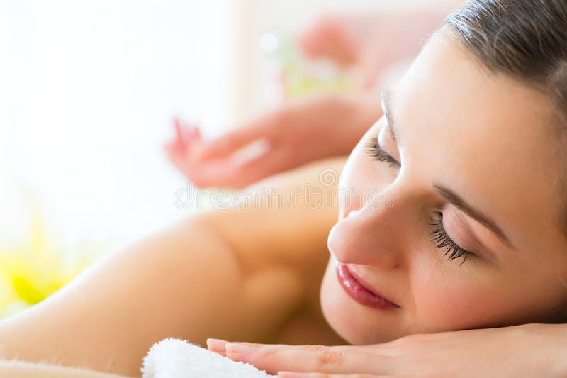Woman having wellness back massage in spa. Beautiful woman having a wellness back massage and feeling visibly good about it stock photography
