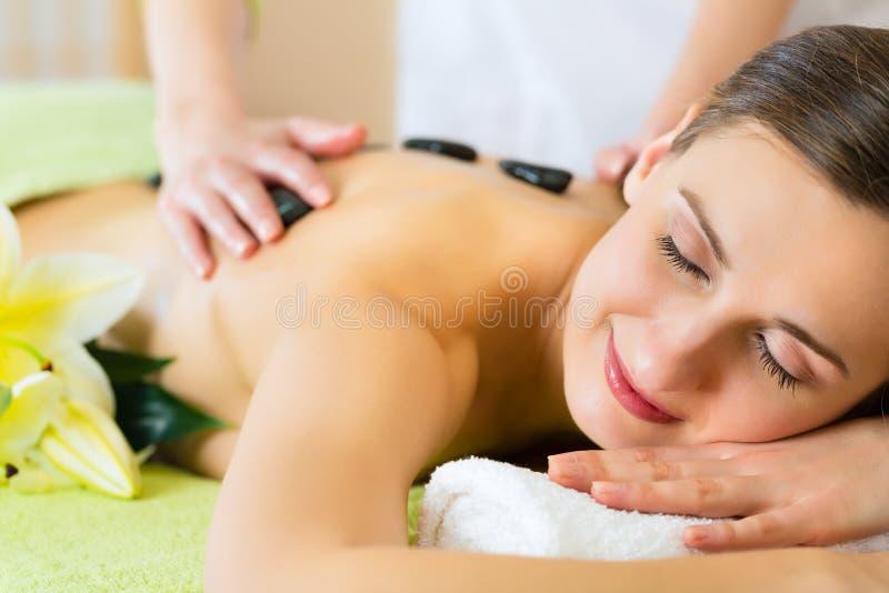 Woman having wellness hot stone massage. Beautiful woman having a wellness hot stone back massage royalty free stock photography