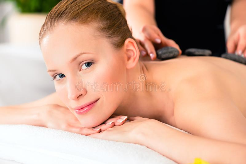 Woman having wellness spa hot stone massage. Woman in wellness beauty spa having hot stone massage, looking relaxed stock image