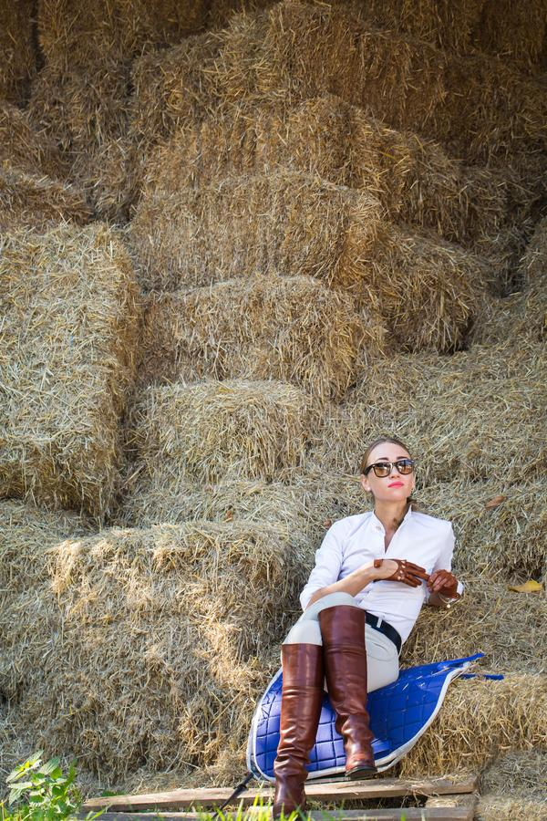Woman on the hayloft. A beautiful woman in a horse riding costume resting in the hayloft stock photography