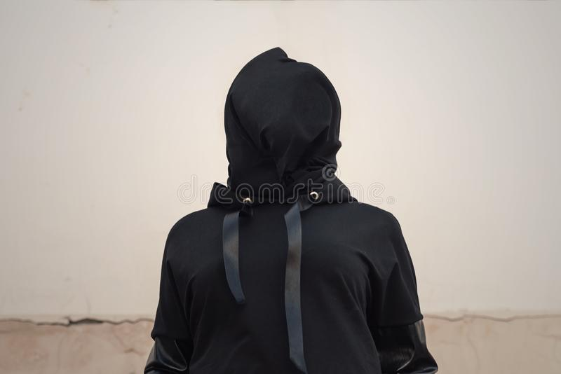 Woman head covered with black textile. Victim, slave, hostage. Woman with veiled face. The concept of kidnapping, detention, and stock photography