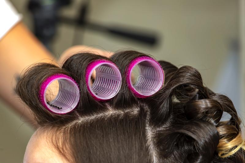 Woman head with hair curled on large curlers. Close-up royalty free stock photo