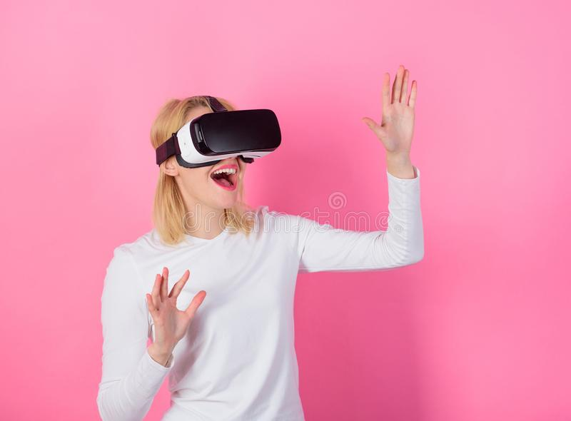 Woman head mounted display pink background. Virtual reality and future technologies. Girl use modern technology vr. Headset. Digital device benefits stock photo