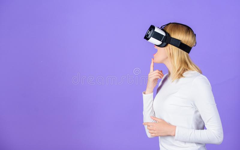 Woman head mounted display violet background. Virtual reality and future technologies. Girl use modern technology vr. Headset. Digital device and modern stock image